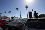 Two women listen to music as they sit through their sunroof in a beach parking lot Thursday, May 21, 2020, in San Diego. San Diego County began to relax rules regarding social distancing and efforts to slow the spread of the new coronavirus Thursday, as restaurant workers and some retail workers scrambled to prepare for limited indoor dining and shopping. (AP Photo/Gregory Bull)