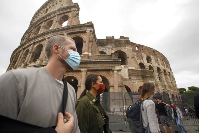 People wear face masks to prevent the spread of COVID-19 as they stroll by the ancient Colosseum, in Rome, Saturday, Oct. 3, 2020. As of Saturday it is mandatory to wear masks outdoors in Lazio, the region that includes Rome. (AP Photo/Andrew Medichini)