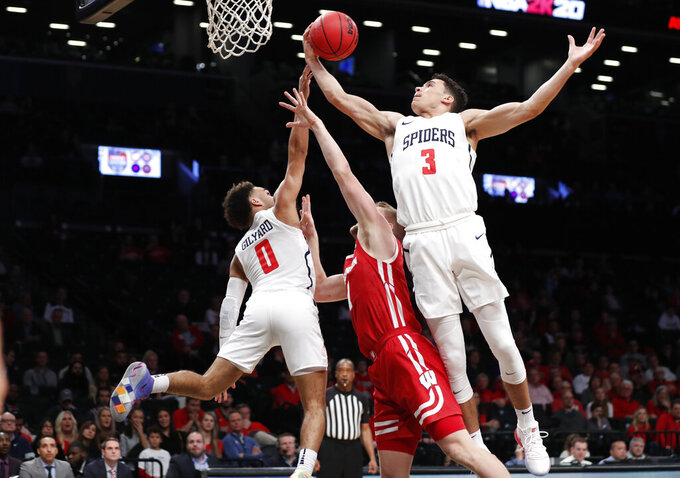 Richmond forward Tyler Burton (3) grabs a rebound as Richmond guard Jacob Gilyard (0) tips the ball toward him and away from Wisconsin guard Brevin Pritzl (1) during the first half of an NCAA college basketball game in the Legends Classic, Monday, Nov. 25, 2019, in New York. (AP Photo/Kathy Willens)