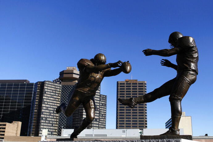 FILE - This Thursday, Nov. 8, 2012 file photo shows the bronze statue titled 'Rebirth,' which shows former New Orleans Saint Steve Gleason blocking a punt against the Atlanta Falcons outside the Mercedes-Benz Superdome in New Orleans. The half-century-old rivalry between the Atlanta Falcons and New Orleans Saints produced a moment so poignant that a statue was placed outside the Superdome to commemorate it.  (AP Photo/Gerald Herbert, File)
