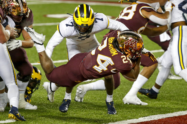 Minnesota running back Mohamed Ibrahim (24) leaps for a touchdown past Michigan defensive back Makari Paige (7) in the third quarter of an NCAA college football game Saturday, Oct. 24, 2020, in Minneapolis. (AP Photo/Bruce Kluckhohn)