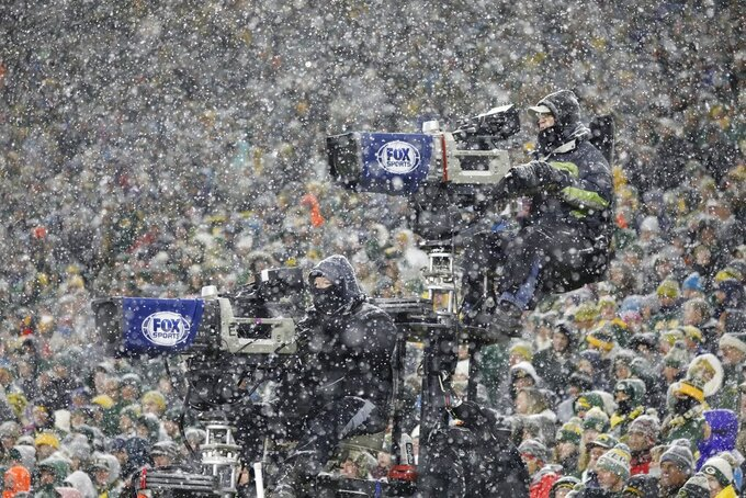 Television cameras are seen through the snow during the second half of an NFL football game between the Green Bay Packers and the Carolina Panthers Sunday, Nov. 10, 2019, in Green Bay, Wis. The Packers won 24-16. (AP Photo/Jeffrey Phelps)