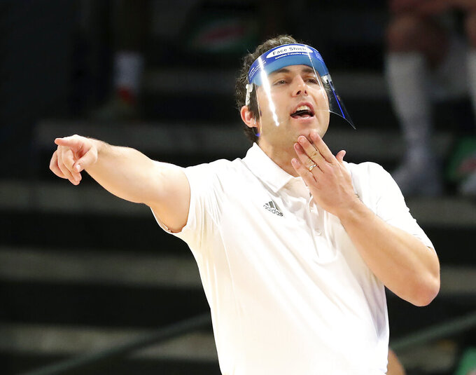 Georgia Tech head coach Josh Pastner wears a face shield while coaching his team against Georgia State during the first half of an NCAA college basketball game, Wednesday, Nov. 25, 2020 in Atlanta. (Curtis Compton/Atlanta Journal-Constitution via AP)