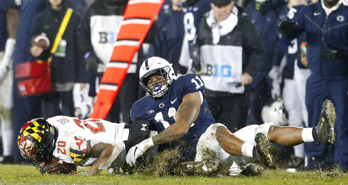 FILE - In this Nov. 24, 2018, file photo, Penn State's Micah Parsons (11) drags down Maryland's Javon Leake (20) for a loss during the second half of an NCAA college football game in State College, Pa. Last year, Micah Parsons put together the greatest freshman season for a linebacker in Penn State history while only starting one game. He learned that making a bunch of tackles wasn't enough to be a starter. (AP Photo/Chris Knight, File)