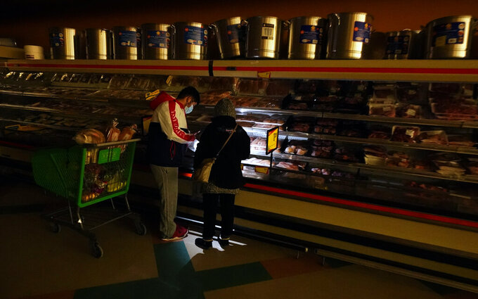 FILE - In this Feb. 16, 2021, file photo, customers use the light from a cell phone to look in the meat section of a grocery store in Dallas. Even though the store lost power, it was open for cash only sales. (AP Photo/LM Otero, File)