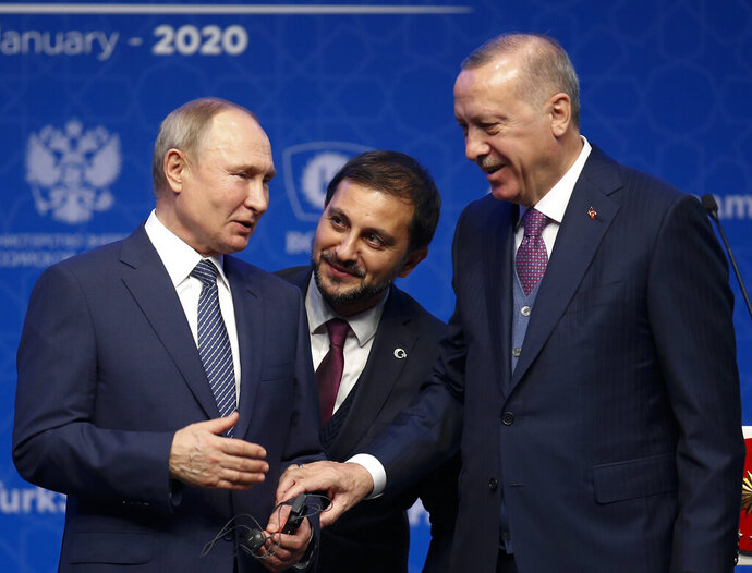 Turkey's President Recep Tayyip Erdogan, right and Russia's President Vladimir Putin, left, talk after they symbolically open a valve during a ceremony in Istanbul for the inauguration of the TurkStream pipeline, Wednesday, Jan. 8, 2020. Man in the centre is an interpreter.The dual natural gas line connecting the countries will open up a new export path for Russian gas into Turkey and Europe, through new and existing lines. (AP Photo/Lefteris Pitarakis)