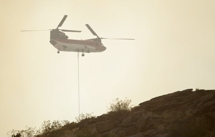Fire crews with a helicopter from around Washington County fight a wildfire near Leeds, Utah. Sunday, July 19, 2020. (Chris Caldwell/The Spectrum via AP)