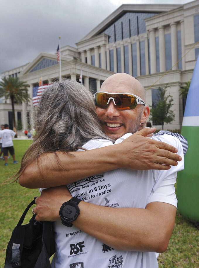 Local attorney Mike Freed, right, gets a hug after he finished a six-day, six marathon run from Tallahassee at the Duval County Courthouse, Friday, June 2, 2017, in Jacksonville, Fla. His run raised money and awareness for Jacksonville Area Legal Aid. (Will Dickey/The Florida Times-Union via AP)