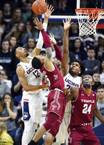Temple's Nate Pierre-Louis (15) is defended by Connecticut's Tyler Polley (12) and Connecticut's Josh Carlton (25) in the second half of an NCAA college basketball game, Thursday, March 7, 2019, in Storrs, Conn. (AP Photo/Stephen Dunn)