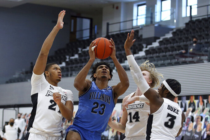 Villanova's Jermaine Samuels (23) drives to the basket against Providence's Ed Croswell (21), Noah Horchler (14) and David Duke (3) during an NCAA college basketball game in Providence, R.I., Saturday, March 6, 2021. (AP Photo/Stew Milne)
