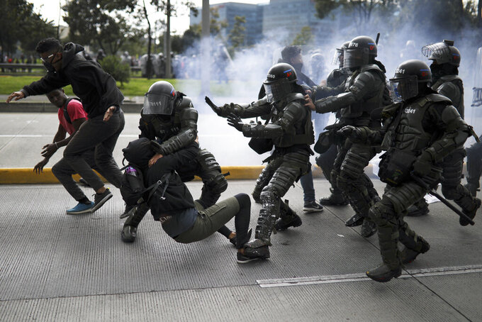 In this Thursday, Nov. 21, 2019 photo, police detain an anti-government demonstrator during a nationwide strike in Bogota, Colombia. Colombia's main union groups and student activists called for a strike to protest the economic policies of Colombian President Ivan Duque government and a long list of grievances. (AP Photo/Ivan Valencia)