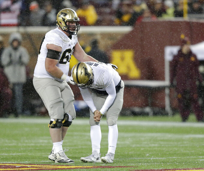 Purdue quarterback David Blough (11) is consoled by Purdue tackle Eric Swingler (60) after Purdue turned the ball over on downs during the third quarter against Minnesota in a NCAA college football game Saturday, Nov. 10, 2018, in Minneapolis. (AP Photo/Andy Clayton-King)