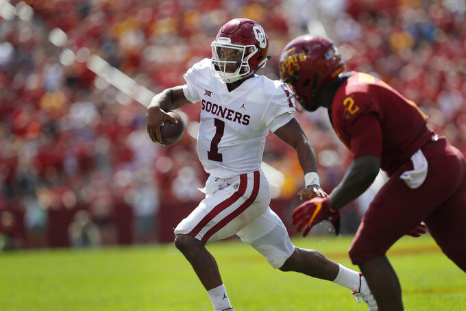 Oklahoma quarterback Kyler Murray, center, runs the ball as he is chased to the sidelines by Iowa State linebacker Willie Harvey, right, during the second half of an NCAA college football game, Saturday, Sept. 15, 2018, in Ames, Iowa. Oklahoma won 37-27. (AP Photo/Matthew Putney)