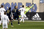 A shot by New England Revolution's Adam Buksa, obscured, sails past goalkeeper Philadelphia Union goalie Andre Blake during an MLS soccer playoff match Tuesday, Nov. 24, 2020, in Chester, Pa. (Charles Fox/The Philadelphia Inquirer via AP)