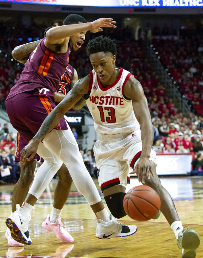 North Carolina State's C.J. Bryce (13) drives against Virginia Tech's Kerry Blackshear Jr., left, during the first half of an NCAA college basketball game in Raleigh, N.C., Saturday, Feb. 2, 2019. (AP Photo/Ben McKeown)