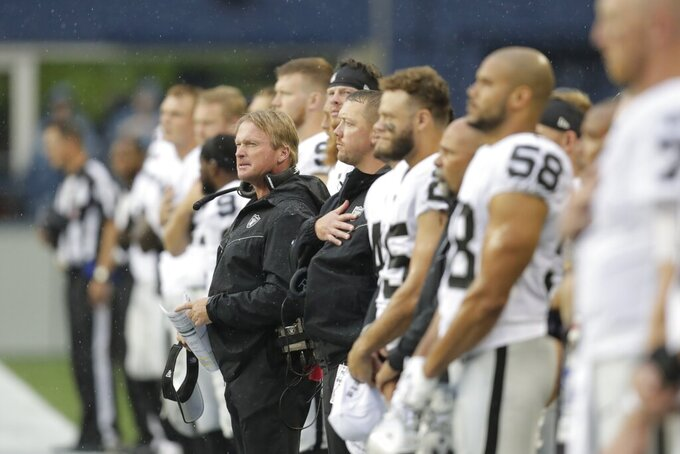 Oakland Raiders head coach Jon Gruden, center, stands with his players during the singing of the national anthem before an NFL football preseason game against the Seattle Seahawks, Thursday, Aug. 29, 2019, in Seattle. (AP Photo/Stephen Brashear)