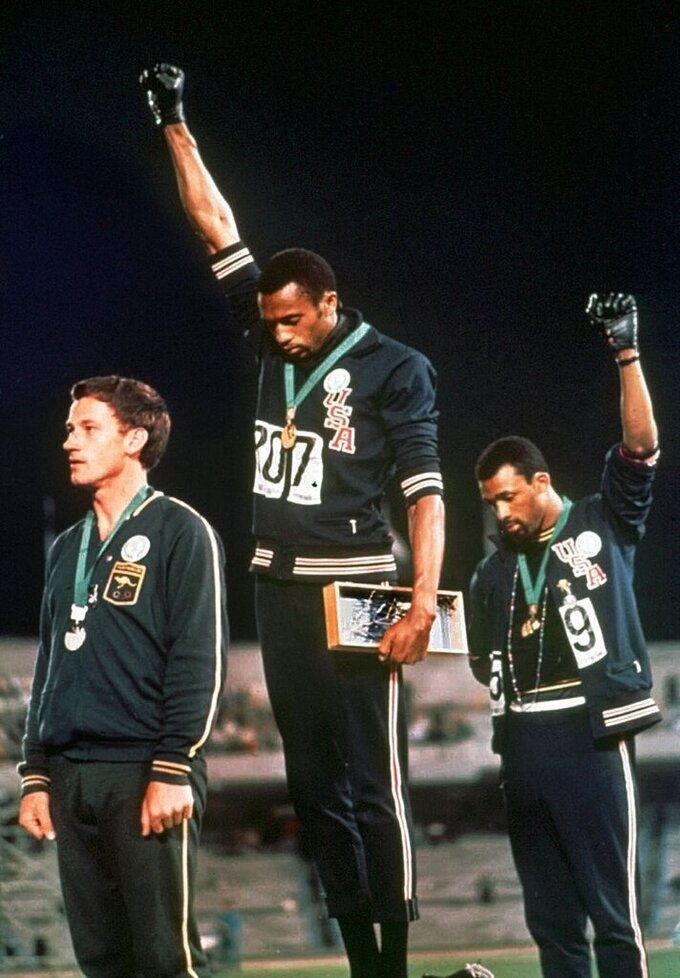 FILE - In this Oct. 16, 1968, file photo, U.S. athletes Tommie Smith, center, and John Carlos extend gloved hands skyward in racial protest during the playing of national anthem after Smith received the gold and Carlos the bronze for the 200 meter run at the Summer Olympic Games in Mexico City. Australian silver medalist Peter Norman is at left. The U.S. Olympic and Paralympic Committee heeded calls from American athletes, announcing Thursday, Dec. 10, 2020, that it won't sanction them for raising their fists or kneeling on the medals stand at next year's Tokyo Games and beyond. (AP Photo/File)
