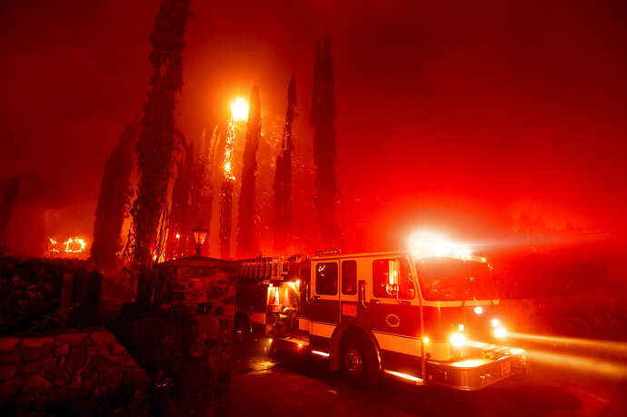 A fire engine leaves a burning property as the Glass Fire tears through St. Helena, Calif., on Sunday, Sept. 27, 2020. (AP Photo/Noah Berger)
