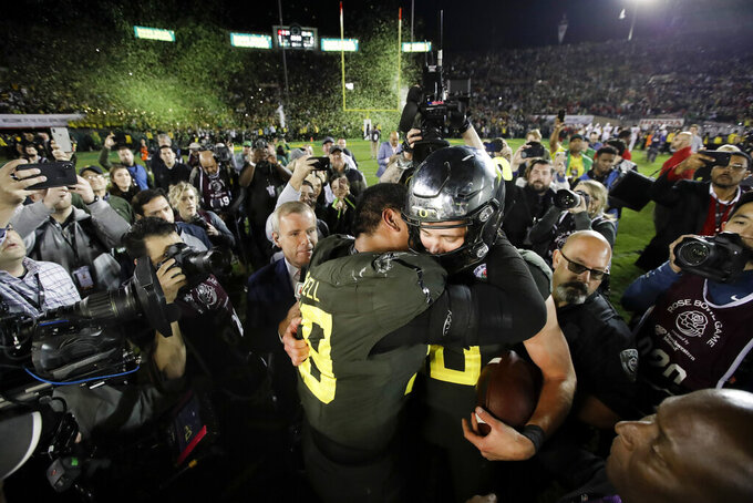 Oregon quarterback Justin Herbert, right, hugs offensive lineman Penei Sewell after their win against Wisconsin in the Rose Bowl NCAA college football game Wednesday, Jan. 1, 2020, in Pasadena, Calif. (AP Photo/Marcio Jose Sanchez)