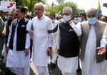 Pakistan's President Arif Alvi, second right, Foreign Minister Shah Mahmood Qureshi, third right, and parliamentarians attend a rally to show solidarity with the Kashmiri people on the eve of the first anniversary of India's decision to revoke the disputed region's semi-autonomy, in Islamabad, Pakistan, Wednesday, Aug. 5, 2020. Last year on Aug. 5, India's Hindu-nationalist-led government of Prime Minister Narendra Modi stripped Jammu and Kashmir's statehood, scrapped its separate constitution and removed inherited protections on land and jobs. (AP Photo/A.H. Chuadary)