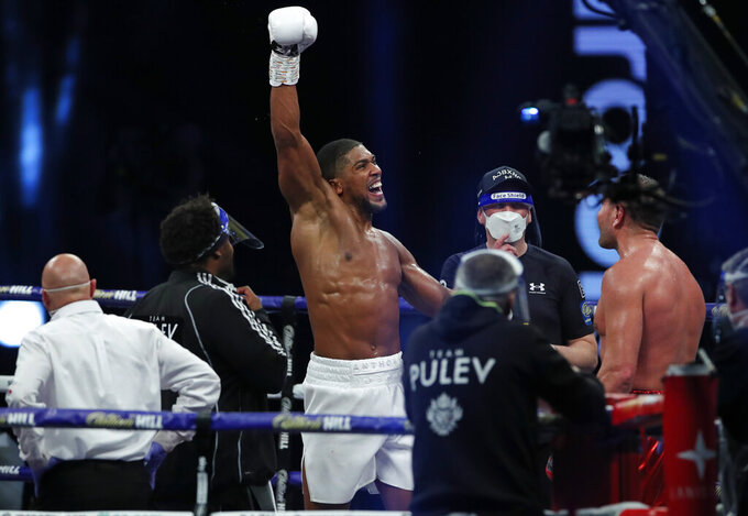 FILE - In this Saturday, Dec. 12, 2020 file photo, World Heavyweight boxing champion Britain's Anthony Joshua celebrates after beating challenger Bulgaria's Kubrat Pulev to win their Heavyweight title fight at Wembley Arena in London.  Joshua will defend his WBA, IBF and WBO heavyweight titles against former undisputed world cruiserweight champion Oleksandr Usyk at Tottenham Hotspur Stadium on Sept. 25. The fight pits two 2012 London Olympic gold medallists against each other. Joshua topped the podium in the super-heavyweight division and Usyk reigned supreme in the heavyweight bracket. (Andrew Couldridge/Pool via AP, File)