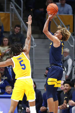 West Virginia's Emmitt Matthews Jr. (11) shoots for three points as Pittsburgh's Au'Diese Toney (5) defends during the first half of an NCAA college basketball game, Friday, Nov. 15, 2019, in Pittsburgh. (AP Photo/Keith Srakocic)