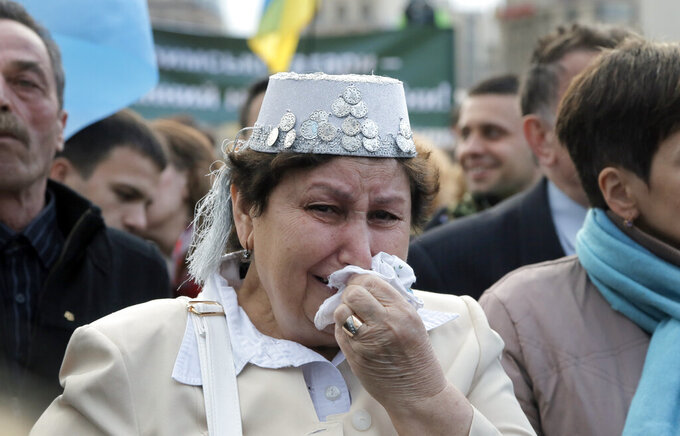 FILE - In this May 18, 2016 file photo, a Crimean Tatar woman in a national costume wipes away her tears at a rally to mark the 72nd anniversary of the deportation of Crimean Tatars in Kyiv, Ukraine, Wednesday, May 18, 2016. The fate of Crimean Tatars is one of the top issues at the inaugural meeting of the Crimean Platform on Monday Aug. 23, 2021, an international summit called by Ukraine to build up pressure on Russia over the annexation that has been denounced as illegal by most of the world. (AP Photo/Efrem Lukatsky, File)