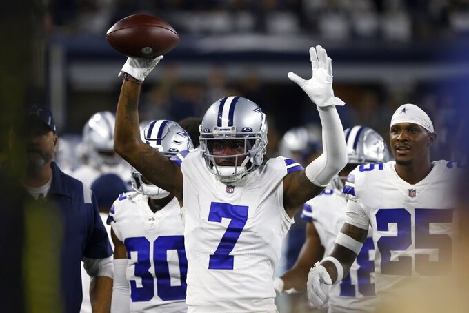 Dallas Cowboys cornerback Trevon Diggs (7) and cornerback Nahshon Wright (25) celebrate on the sideline after Diggs intercepted a Philadelphia Eagles' Jalen Hurts pass and returned it for a touchdown in the second half of an NFL football game in Arlington, Texas, Monday, Sept. 27, 2021. (AP Photo/Ron Jenkins)