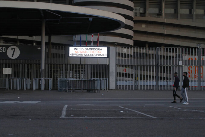 Two people walk by a notice outside San Siro stadium advising that the Serie A soccer match between Inter and Sampdoria is cancelled, in Milan, Italy, Sunday, Feb. 23, 2020. In Lombardy, the hardest-hit region by the spread of the Coronavirus with 90 cases, schools and universities were ordered to stay closed in the coming days, and sporting events were canceled. Lombardy's ban on public events also extended to Masses in churches in the predominantly Roman Catholic nation. (AP Photo/Antonio Calanni)