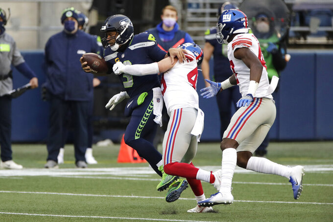 Seattle Seahawks quarterback Russell Wilson, left, is sacked by New York Giants linebacker Carter Coughlin, center, as Cam Brown looks on at right, during the second half of an NFL football game, Sunday, Dec. 6, 2020, in Seattle. (AP Photo/Larry Maurer)