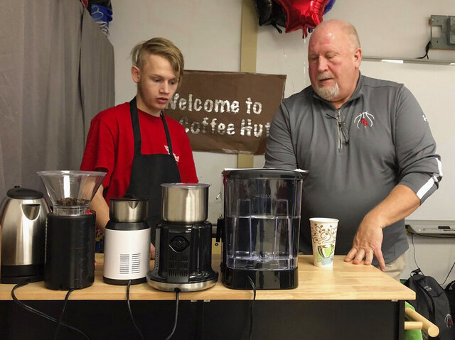 In a Friday, Jan. 31, 2020 photo, Beau Remington works with his teacher, Steve Hilton, to fill a coffee order at Scooper Sam's Awesome Coffee Hut at Sturgis Brown High School in Sturgis.  (Deb Holland/Black Hills Pioneer via AP)