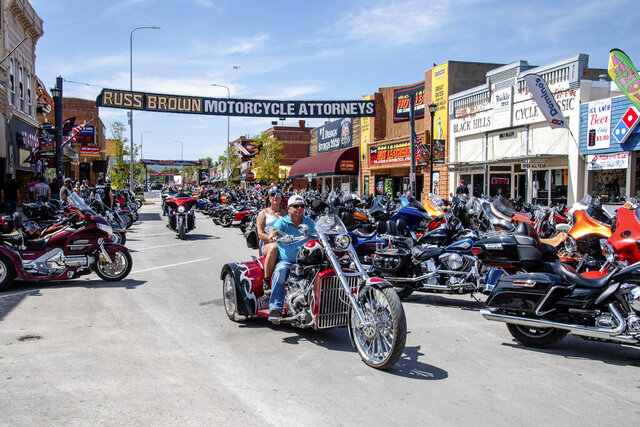 FILE - In this Aug. 15, 2020 file photo, bikers ride down Main Street during the 80th annual Sturgis Motorcycle Rally in Sturgis, S.D.   This summer's huge motorcycle rally in South Dakota led to dozens of coronavirus cases in neighboring Minnesota. That's the finding of a report Friday, Nov. 20,  from the Centers for Disease Control and Prevention. (Amy Harris/Invision/AP)
