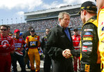 FILE - In this Feb. 15, 2004, file photo, President George W. Bush, left, greets Matt Kenseth, right, as he greets drivers in the pit at Daytona 500 NASCAR race in Daytona Beach, Fla. President Donald Trump will look to rev up his appeal with a key voting demographic Sunday — NASCAR fans — as he takes in the Daytona 500. (AP Photo/Pablo Martinez Monsivais, File)