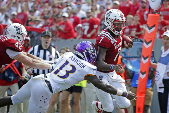North Carolina State quarterback Matthew McKay (7) runs for a touchdown while East Carolina defensive back Davondre Robinson (13) tries to tackle during the second half of an NCAA college football game in Raleigh, N.C., Saturday, Aug. 31, 2019. (AP Photo/Gerry Broome)