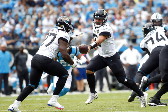 Jacksonville Jaguars quarterback Gardner Minshew (15) hands off to Jacksonville Jaguars running back Leonard Fournette (27) during the first half of an NFL football game against the Carolina Panthers in Charlotte, N.C., Sunday, Oct. 6, 2019. (AP Photo/Brian Blanco)