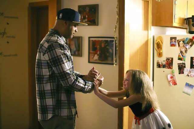 In this Friday, Feb. 7, 2020, photo, Tyran Sampson and his daughter Jaleaha Sampson dance in their living room in Manchester, Conn. Sampson said he was hoping to see his family more when he was staying at a halfway house in Hartford but couldn't. (AP Photo/Chris Ehrmann)