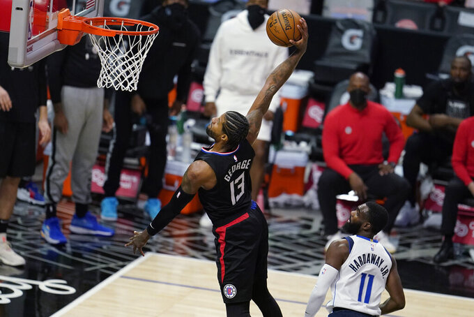 Los Angeles Clippers guard Paul George (13) dunks past Dallas Mavericks forward Tim Hardaway Jr. (11) during the first half in Game 2 of an NBA basketball first-round playoff series Tuesday, May 25, 2021, in Los Angeles. (AP Photo/Marcio Jose Sanchez)