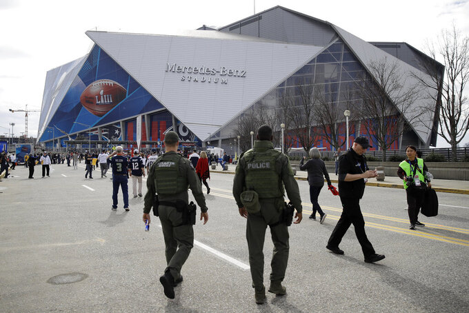 Police officers patrol the grounds around the Mercedes-Benz Stadium, Sunday, Feb. 3, 2019, in Atlanta, ahead of the NFL Super Bowl 53 football game between the Los Angeles Rams and New England Patriots. (AP Photo/Matt Rourke)