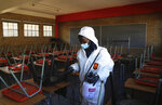 A worker from Bidvest Prestige wearing protective gear, sprays disinfectant in a classroom to help reduce the spread the new coronavirus ahead of the reopening of Landulwazi Comprehensive School, east of Johannesburg, South Africa, Tuesday, May 26, 2020, ahead of the June 1, 2020, re-opening of Grade 7 and 12 learners to school. (AP Photo/Themba Hadebe)