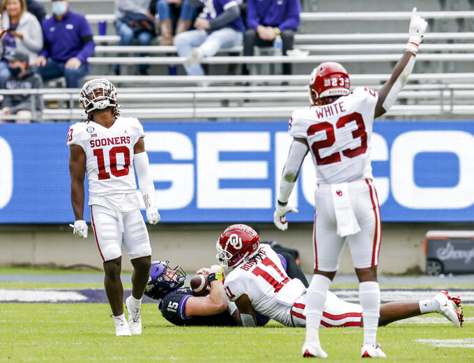 Oklahoma safety Pat Fields (10) and linebacker DaShaun White (23) celebrate linebacker Nik Bonitto's (11) sack of TCU quarterback Max Duggan (15) during the second half of an NCAA college football game, Saturday, Oct. 24, 2020, in Fort Worth, Texas.  (AP Photo/Brandon Wade)