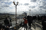 Media crews film the quarantined Diamond Princess cruise ship at a port in Yokohama, near Tokyo, Wednesday, Feb. 19, 2020. The cruise ship begins letting passengers off the boat on Wednesday after it's been in quarantined for 14 days. (AP Photo/Eugene Hoshiko)