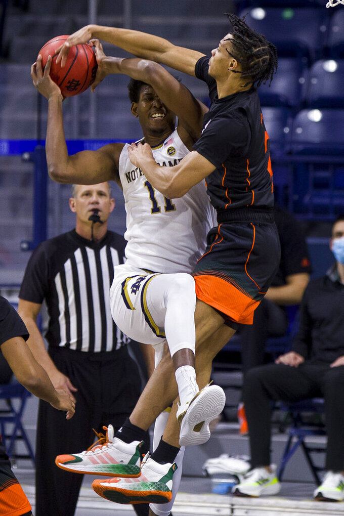 Notre Dame's Juwan Durham (11) goes up to shoot with pressure from Miami's Isaiah Wong (2) during the first half of an NCAA college basketball game Sunday, Feb. 14, 2021, in South Bend, Ind. (AP Photo/Robert Franklin)