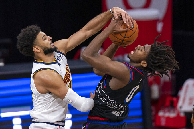 Denver Nuggets' Jamal Murray, left, blocks the shot attempt by Philadelphia 76ers' Tyrese Maxey, right, during the first half of an NBA basketball game, Saturday, Jan. 9, 2021, in Philadelphia. (AP Photo/Chris Szagola)
