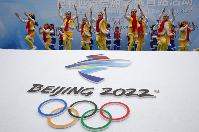 FILE - In this Feb. 27, 2018, file photo, Chinese performers dance during a ceremony to mark the arrival of the Olympic flag and start of the flag tour for the Winter Olympic Games Beijing 2022 at a section of the Great Wall of China on the outskirts of Beijing. Uncertainty surrounds how the postponed Tokyo Olympics will be held next year in the midst of the coronavirus. The same questions permeate three mega-events that will be staged in China within a year after the Tokyo Games close. (AP Photo/Ng Han Guan, File)