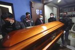 In this photo provided by Peru's Interior Ministry, Justice Minister Anibal Torres, second from left, watches police push the coffin of Abimael Guzman, founder and leader of the Shining Path guerrilla movement, at a crematorium in Callao, Peru, Friday, Sept. 24, 2021. The Peruvian government cremated Guzman on Friday, according authorities. (Rolly Reyna/Peruvian Interior Ministry via AP)