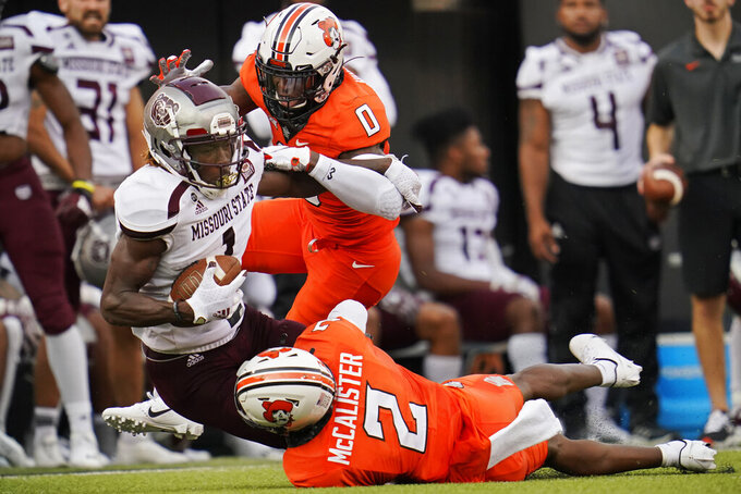 Missouri State wide receiver Xavier Lane (1) is tackled by Oklahoma State cornerback Christian Holmes (0) and safety Tanner McCalister (2) in the first half of an NCAA college football game, Saturday, Sept. 4, 2021, in Stillwater, Okla. (AP Photo/Sue Ogrocki)
