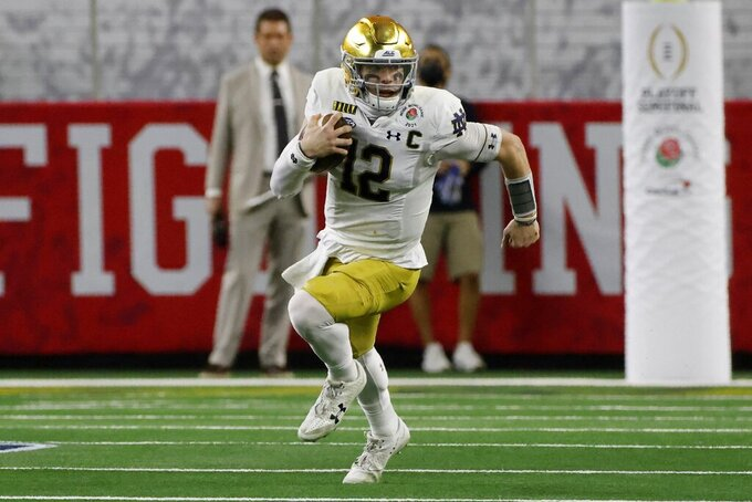 Notre Dame quarterback Ian Book (12) runs the ball against Alabama for a first down in the first half of the Rose Bowl NCAA college football game in Arlington, Texas, Friday, Jan. 1, 2021. (AP Photo/Michael Ainsworth)