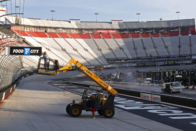 A worker changes a sign in the morning light as a sweeper cleans pit road before practice for an NASCAR Xfinity Series auto race on Friday, Aug. 16, 2019, in Bristol, Tenn. (AP Photo/Wade Payne)