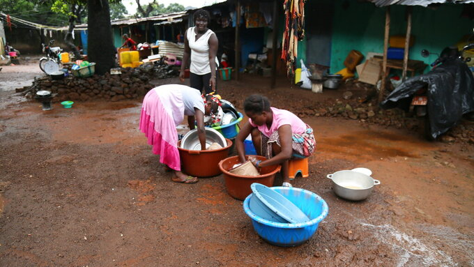 Women wash clothes at the house of Guinean wrestler Fatoumata Yarie Camara in Conakry, Guinea, Tuesday, July 20, 2021. A West African wrestler's dream of competing in the Olympics has come down to a plane ticket. Fatoumata Yarie Camara is the only Guinean athlete to qualify for these Games. She was ready for Tokyo, but confusion over travel reigned for weeks. The 25-year-old and her family can't afford it. Guinean officials promised a ticket, but at the last minute announced a withdrawal from the Olympics over COVID-19 concerns. Under international pressure, Guinea reversed its decision. (AP Photo/Youssouf Bah)