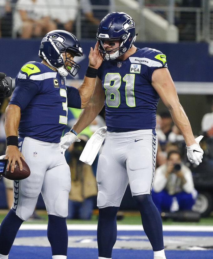Seattle Seahawks quarterback Russell Wilson (3) and tight end Nick Vannett (81) celebrate a touchdown scored on a running play by Wilson during the second half of the NFC wild-card NFL football game agains the Dallas Cowboys, in Arlington, Texas, Saturday, Jan. 5, 2019. (AP Photo/Michael Ainsworth)
